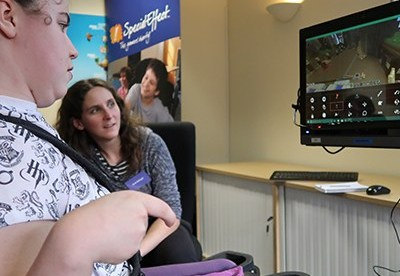 becky seen playing minecraft with her eyes. There is another person sitting next to her watching her gameplay on the monitor.