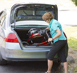 woman putting Rifton Pacer in trunk of car