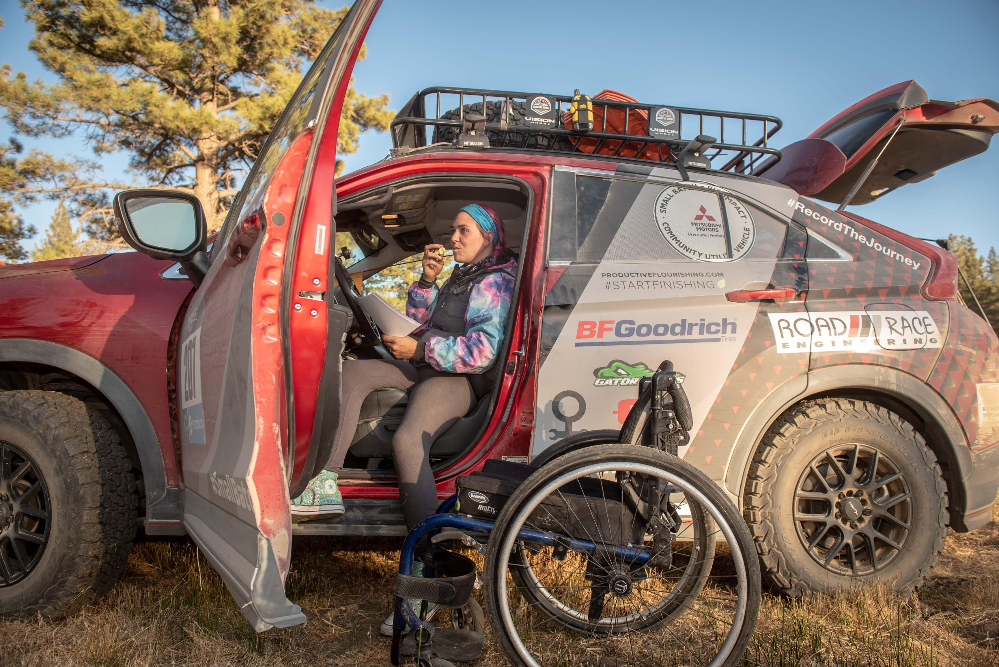 Adaptive off-road athlete Karah Behrend sits in driver seat of SUV with door open and legs hanging out the side of the SUV. Her wheelchair sits in the dirt next to the SUV
