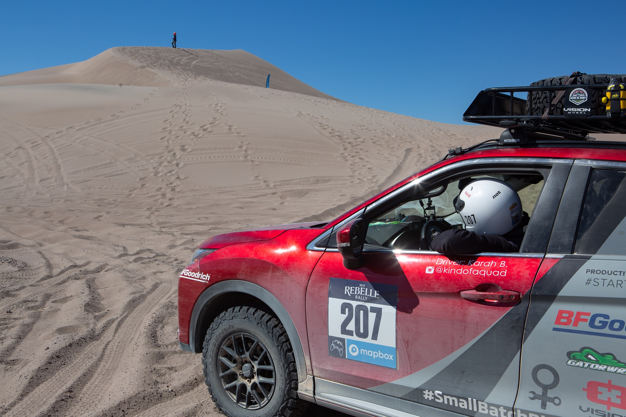 Karah Behrend in white helmet shown in the driver's seat of a red SUV, spotting a line up a sand dune