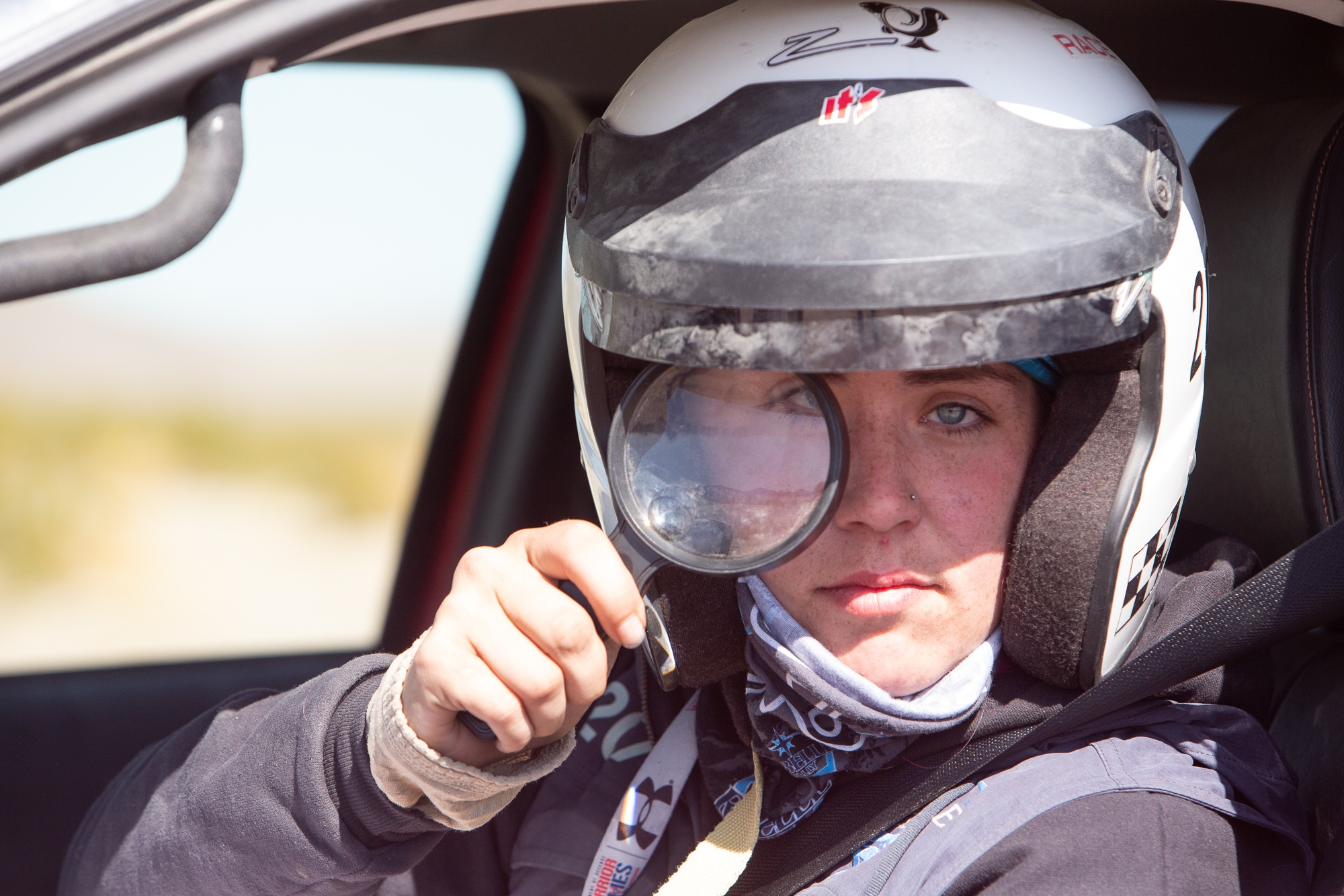 Closeup of adaptive off-road athlete Karah Behrend looking through a magnifying glass at camera while sitting in her vehicle and wearing a white helmet