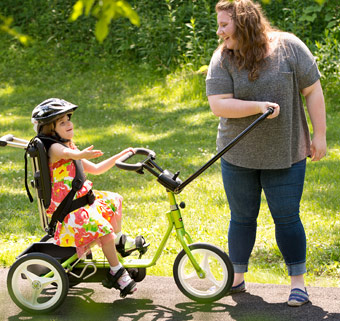 A girl sitting on a Rifton Adaptive Tricycle with a caretaker holding the front guide bar