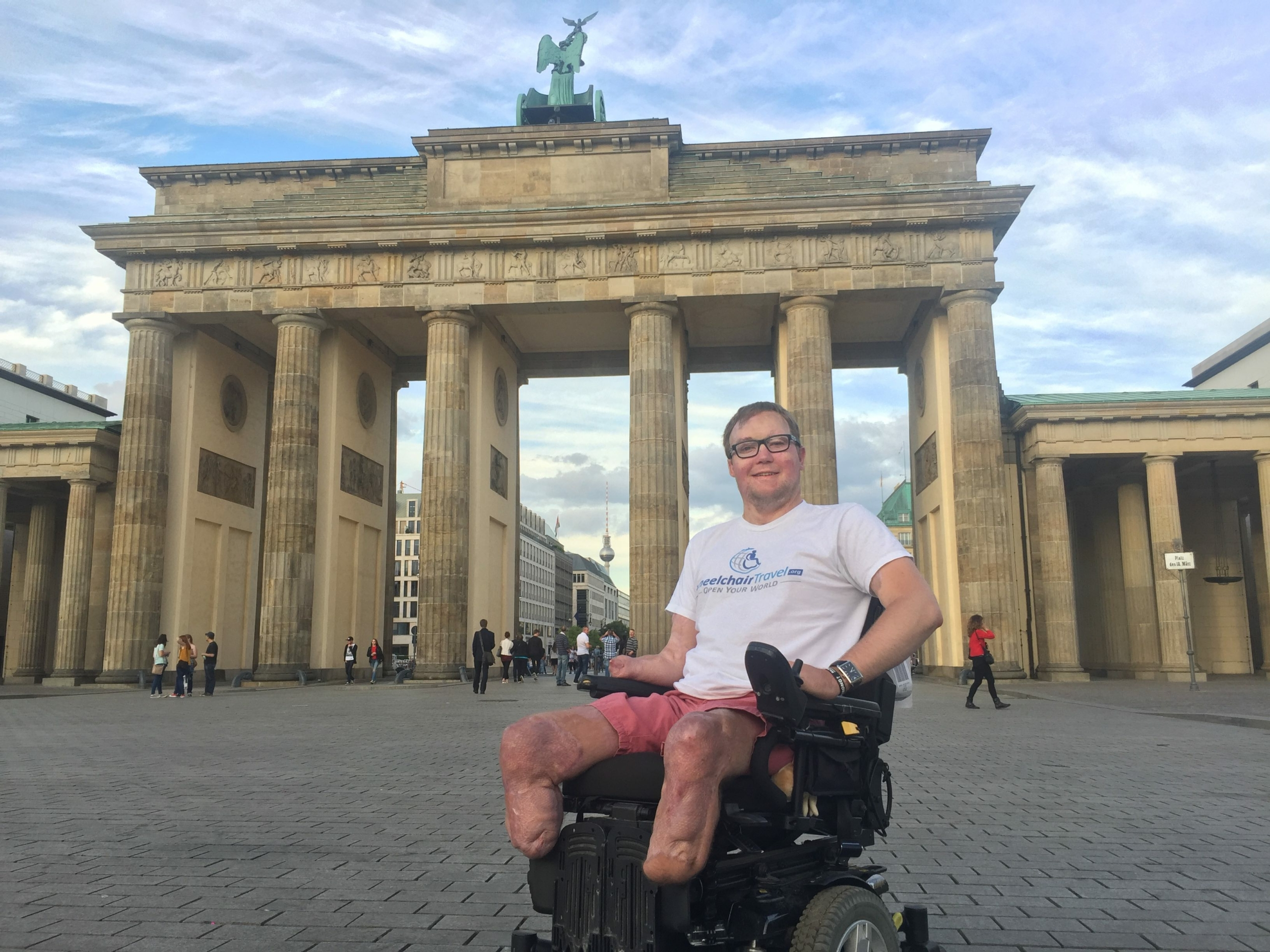 power wheelchair user shown smiling in front of monument